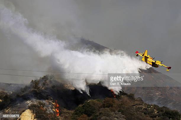 A plane drops water in an attempt to control wildfires burning through hillsides on January 16 2014 in Azusa California Authorities have stated that...