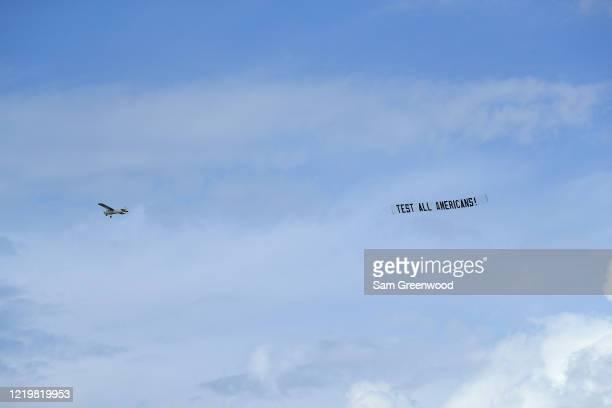 Plane flies a banner over the beach on April 19, 2020 in Jacksonville Beach, Florida. Jacksonville Mayor Lenny Curry announced Thursday that Duval...