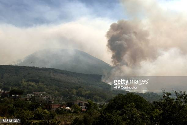 A plane flies above smoke rising from fires on the slopes of Mount Vesuvius east of Naples on July 12 2017 Across the country Italian firefighters...