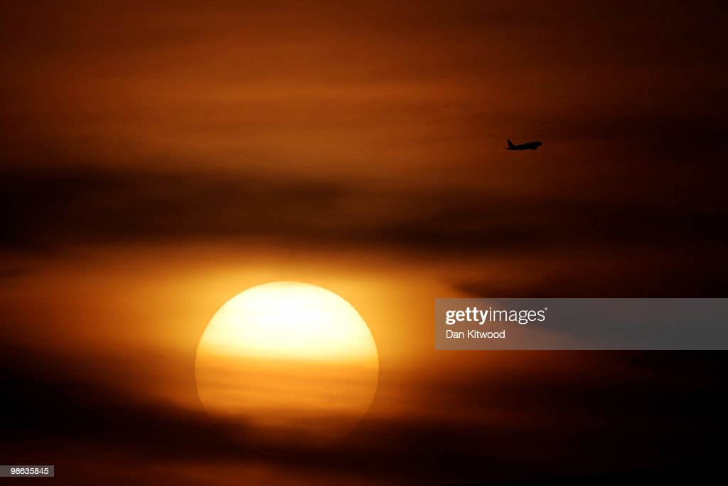 A plane flies above the setting sun on April 23, 2010 in London, United Kingdom. UK airports reopened on Tuesday night when safety test showed aircraft engines were able to cope in low density ash.