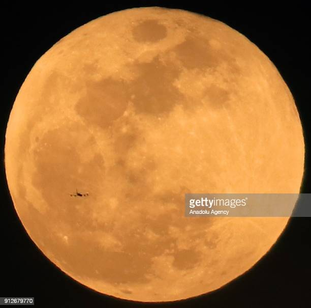 A plane flies in front of the 'Super blue blood moon' in Hatay province of Turkey on January 31 2018 The full moon on January 31st combines three...