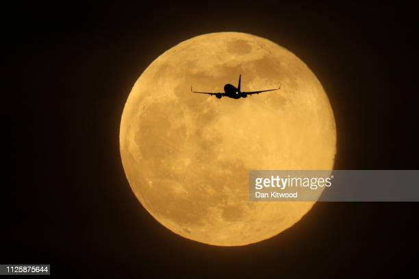 A plane flies in the sky in front of the largest Supermoon of 2019 on February 19 2019 in London England Today's Supermoon sometimes known as the...