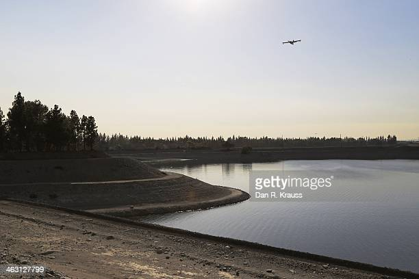 A plane flies over a reservoir as fire emergency services work to control wildfires burning through hillsides on January 16 2014 in Azusa California...