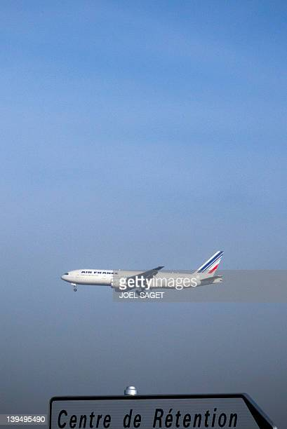 A plane flies over a sign indicating the direction of the immigrant detention centre of MesnilAmelot Paris suburb on February 22 2012 AFP PHOTO /...