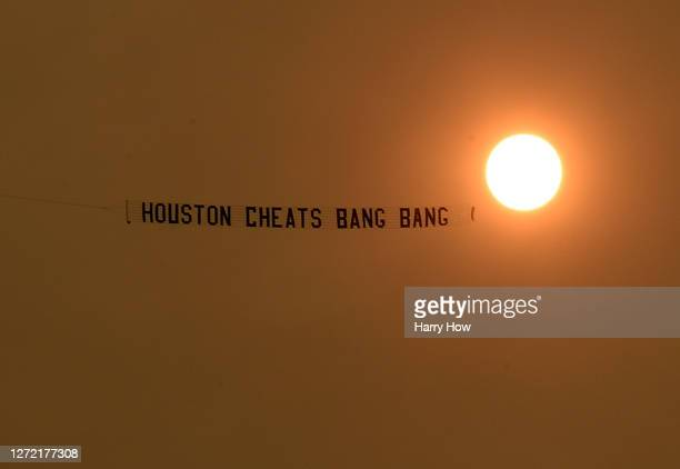 Plane flies over pulling a banner directed at the Houston Astros before the game against the Los Angeles Dodgers at Dodger Stadium on September 12,...