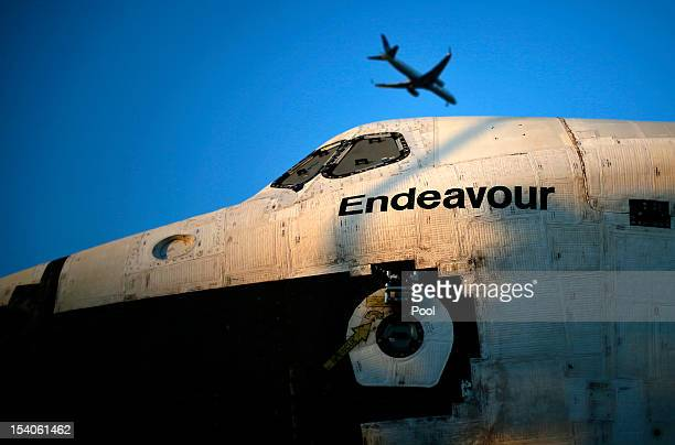 A plane flies over the Space Shuttle Endeavour as it is moved to the California Science Center on October 13 2012 in Inglewood California The space...