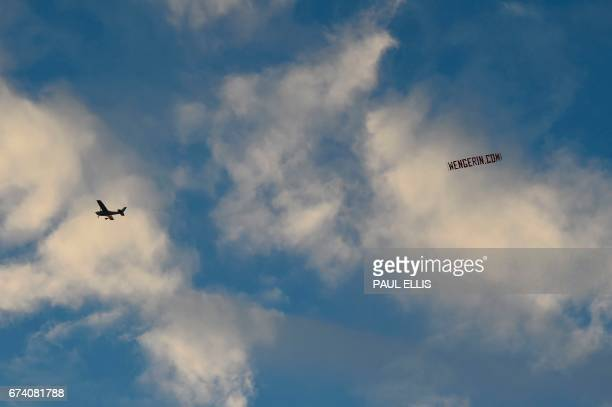 A plane flies over the stadium trailing a sign that reads 'wengerincom' referring to Arsenal's French manager Arsene Wenger during the English...