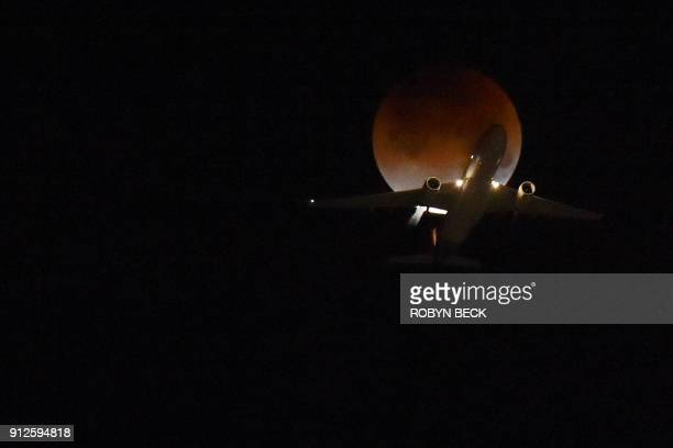 A plane flies passing the moon over Los Angeles California on January 31 2018 Many parts of the globe may catch a glimpse on January 31 of a giant...