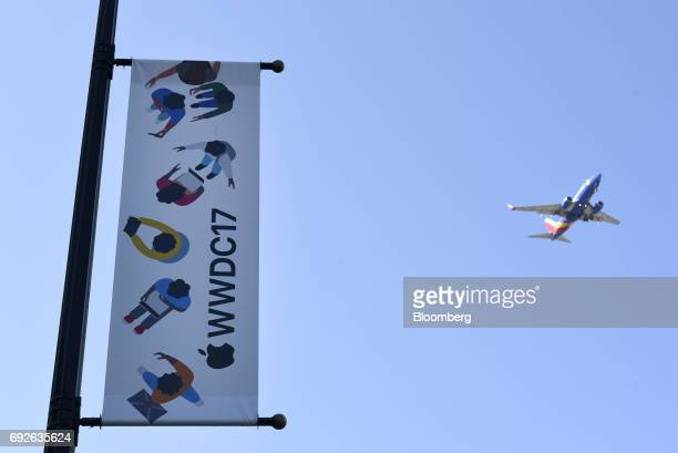 A plane flies past signage displayed outside of the McEnery Convention Center during the Apple Worldwide Developers Conference in San Jose California...
