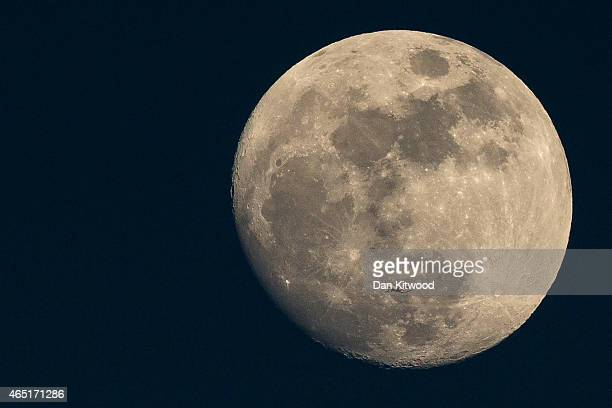 A plane flies past the moon at sunset on March 3 2015 in London England