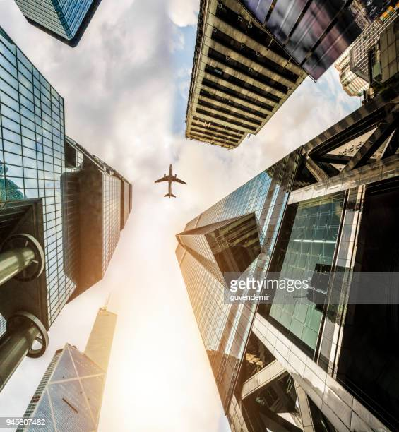 plane fly on business towers in hongkong - diminishing perspective stock pictures, royalty-free photos & images