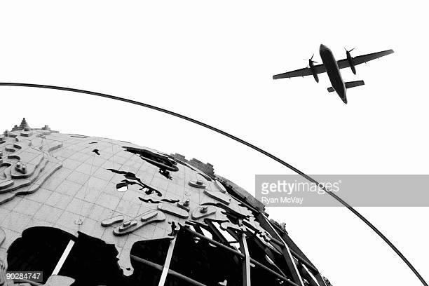 Plane flying above World's Fair Globe, New York