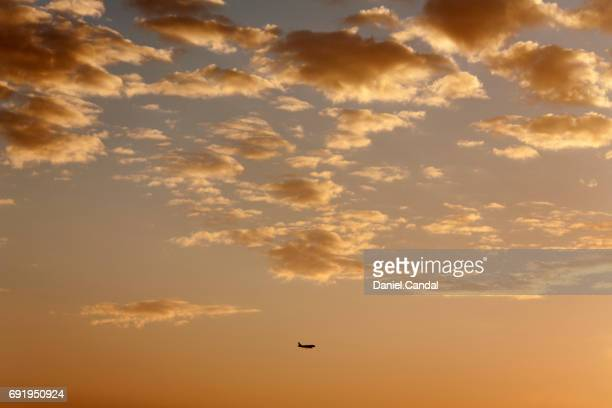 Plane flying over a cloudy sky during sunrise
