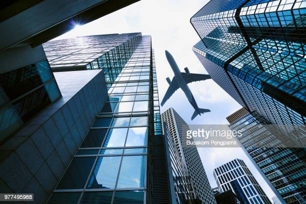 a plane flying over modern office buildings in central hong kong. - oost azië stockfoto's en -beelden