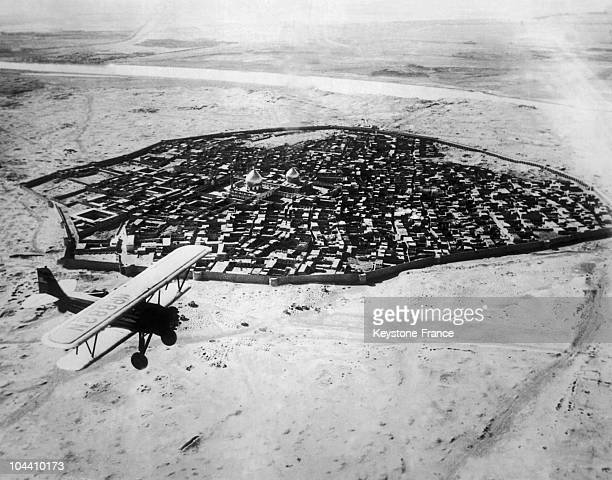 A plane flying over the old town of Baghdad Iraq around the 1930s