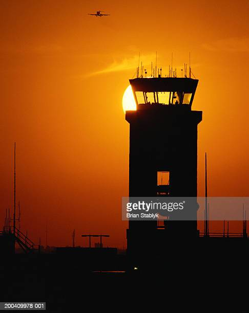 Plane flying past aircraft control tower, sunset