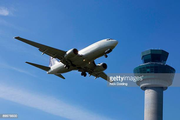 Plane flying past control tower