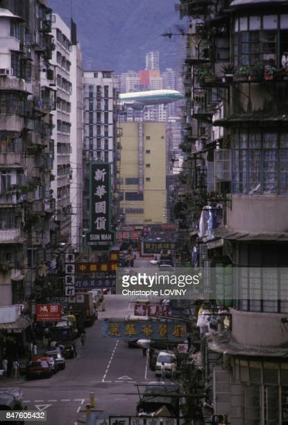 A plane flying very close to the tops of buildings before landing at Kai Tak airport in Hong Kong circa 1980 in Hong Kong