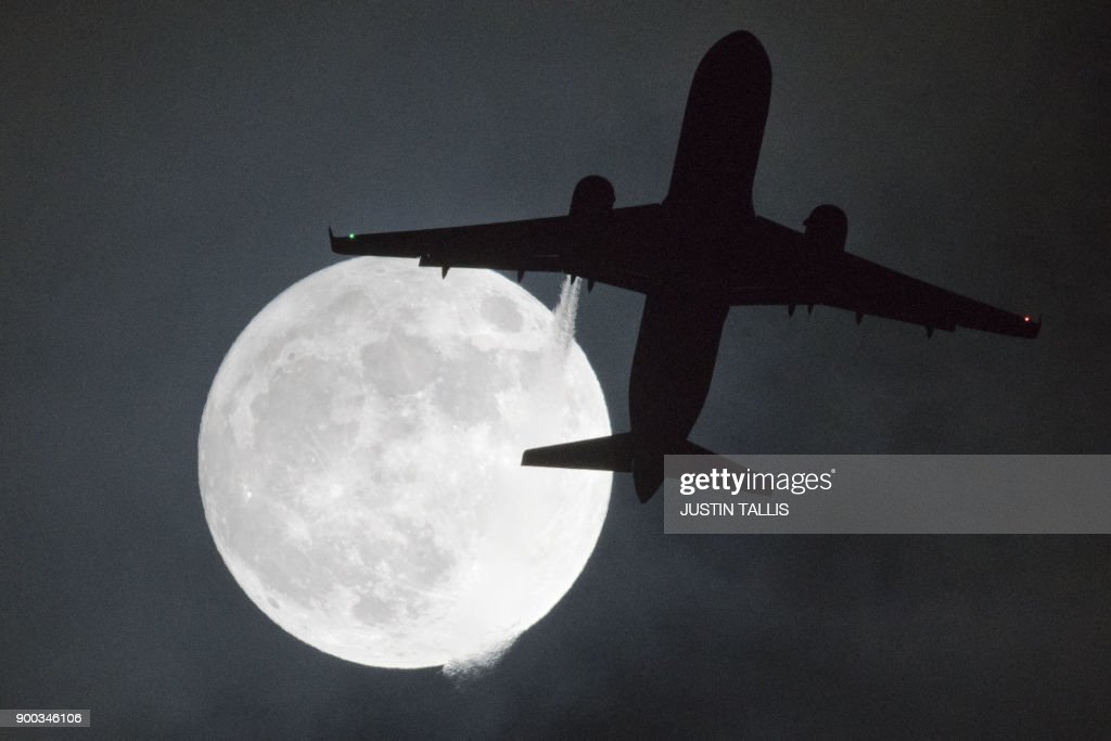 TOPSHOT - A plane flys in front of a 'super moon' or 'wolf moon' on its approach to London Heathrow Airport on January 1, 2018. / AFP PHOTO / Justin TALLIS