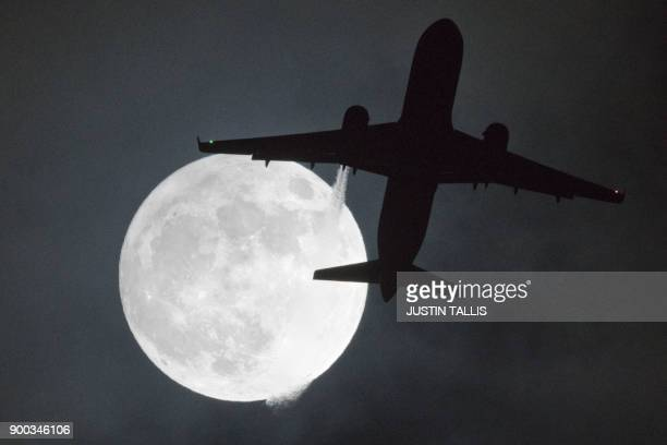 TOPSHOT A plane flys in front of a super moon or wolf moon on its approach to London Heathrow Airport on January 1 2018 / AFP PHOTO / Justin TALLIS