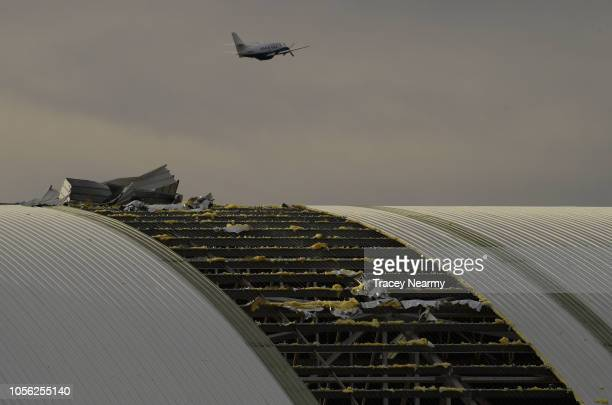 A plane flys over the damaged airport hangar roof that was ripped off in the storm that hit Canberra on November 2 2018 in Canberra Australia Strong...