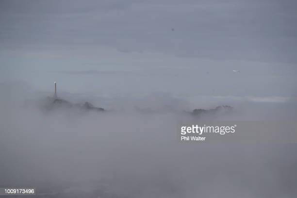 A plane flys over the top of One Tree Hill as fog blankets the city on August 2 2018 in Auckland New Zealand Fog restrictions at Auckland Airport...