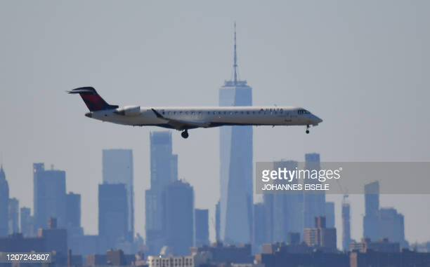 Plane from Delta airline is seen above the skyline of Manhattan before it lands at JFK airport on March 15, 2020 in New York City. - Chaos gripped...