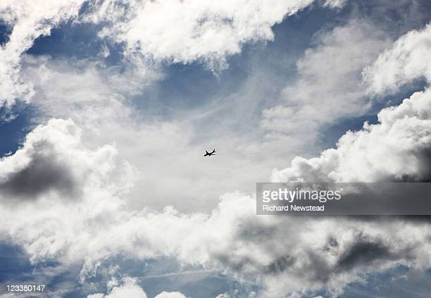 plane in dramatic cloud filled sky - image stock pictures, royalty-free photos & images