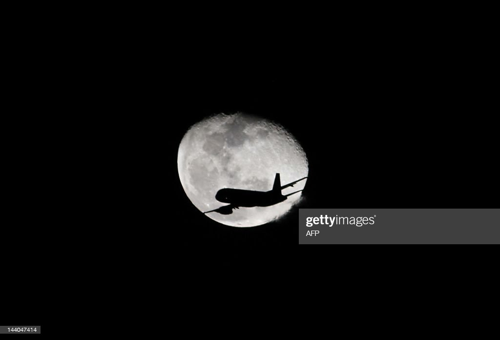 A plane in flight is silhouetted against the moon on May 8, 2012 over Bogota, Colombia. AFP PHOTO/Felipe Caicedo / AFP PHOTO / Felipe CAICEDO