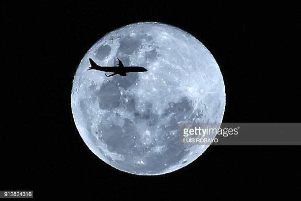 TOPSHOT A plane in flight is silhouetted against the 'super blue moon' over Cali Colombia on January 31 2018 Skywatchers witnessed a rare lunar...