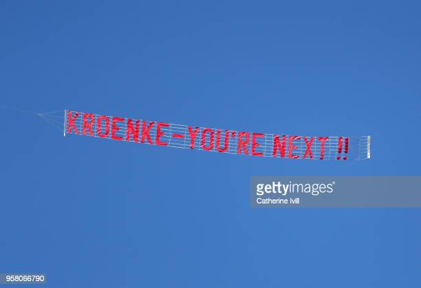 A plane is seen flying a sign reading 'Kroenke youre next' during the Premier League match between Huddersfield Town and Arsenal at John Smith's...