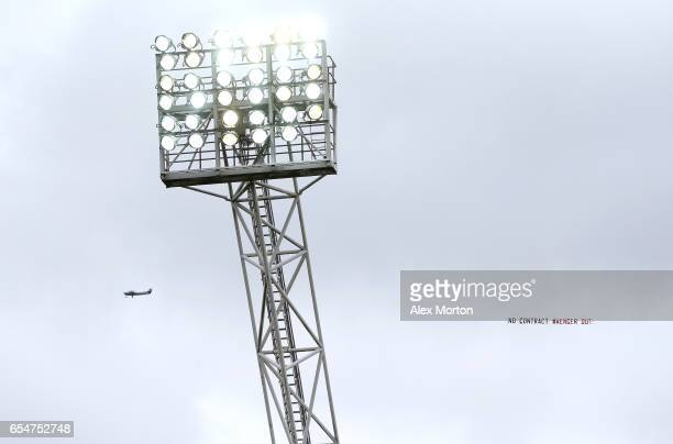 A plane is seen flying over the stadium dispalying a message about Arsene Wenger Manager of Arsenal during the Premier League match between West...
