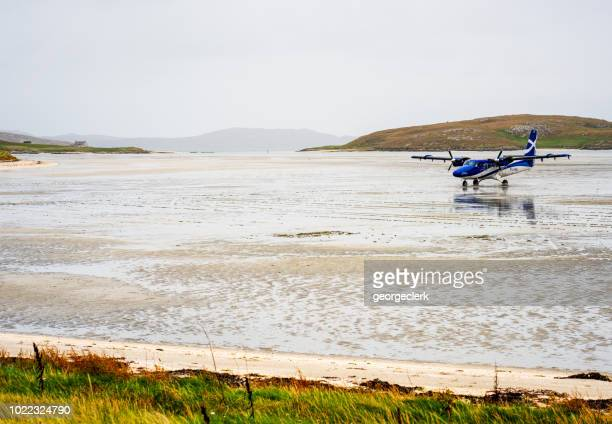 plane landing on barra's unusual beach runway - barra scotland stock pictures, royalty-free photos & images