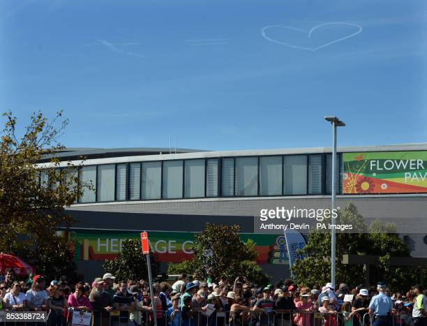 A plane leaves a vapour trail display in the air as the Duke and Duchess of Cambridge visit the Royal Easter Show at Sydney Olympic Park during the...
