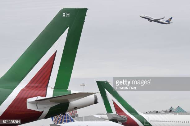 A plane of lowcost airline company Ryanair takesoff as planes of the Italian airline company Alitalia are parked at Rome's Fiumicino airport on April...