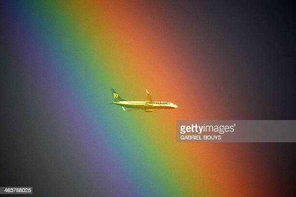 A plane of the Irish low cost company Ryanair flies in front of a rainbow over Rome on January 19 2014 AFP PHOTO / GABRIEL BOUYS