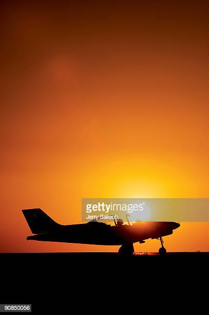 Plane on runway at sunset