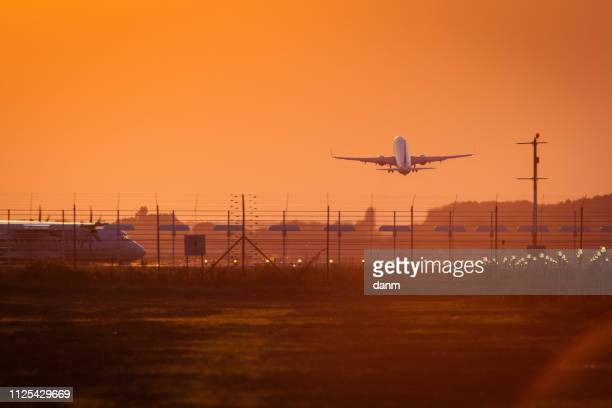 plane on the track preparing to take off at sunset with red sky in background in same time with other taking off - bucharest stock pictures, royalty-free photos & images