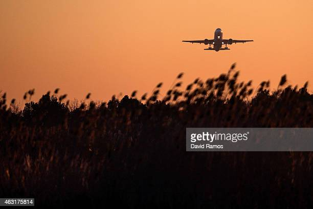 A plane operated by Vueling Airlines departs from Aena operated Barcelona El Prat International Airport at sunrise on February 10 2015 in Barcelona...