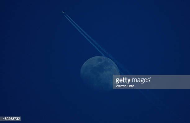 A plane passes across the moon during the third round of the Omega Dubai Desert Classic on the Majlis Course at the Emirates Golf Club on January 31...