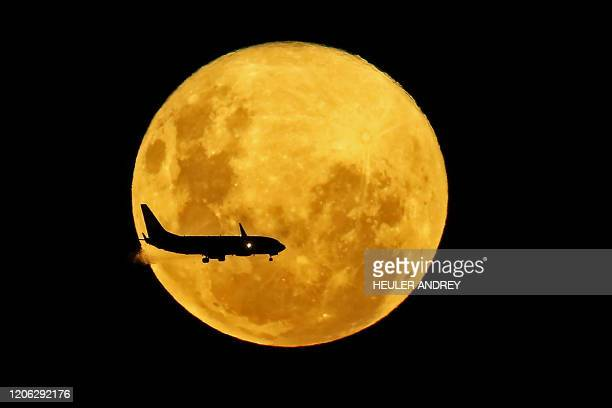 A plane passes in front of the full moon as seen from Curitiba Brazil on March 9 2020 The supermoon is visible as the full moon coincides with the...