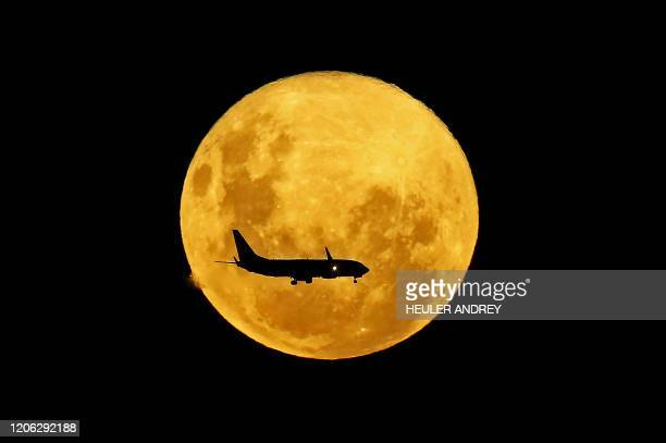 TOPSHOT A plane passes in front of the full moon as seen from Curitiba Brazil on March 9 2020 The supermoon is visible as the full moon coincides...