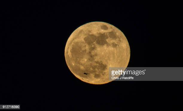 A plane passes supermoon as it rises over London on January 31 2018 in London United Kingdom The super blue blood moon is a rare combination of a...