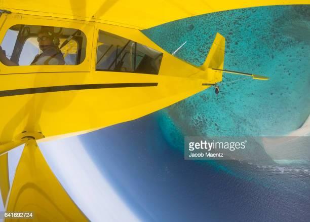 Plane performs an aerobatics maneuver over tropical reef.