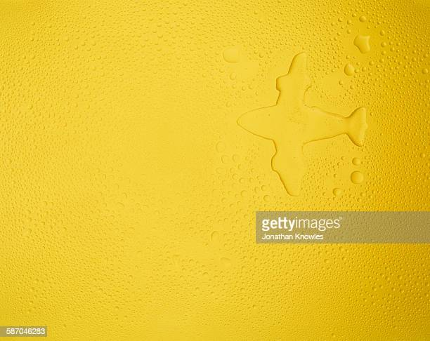 Plane shape on yellow background with condensation