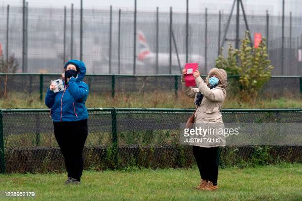 Plane spotters photograph and watch a British Airways Boeing 747 aircraft as it makes a flypast over London Heathrow airport on it's final flight, in...