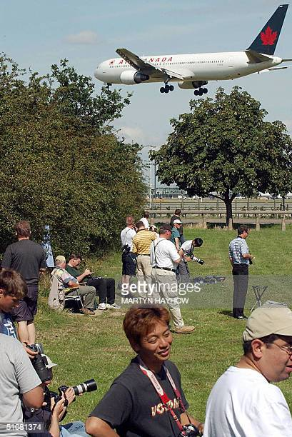 Plane spotters stand 19 July 2004 near the perimeter fence of Heathrow airport's ring road system Fears about terrorism returned to haunt Britain on...