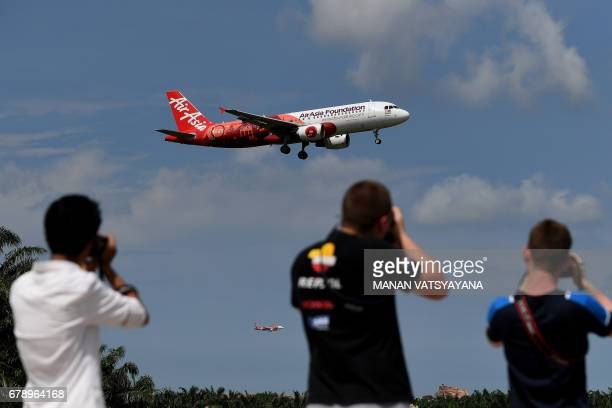 Plane spotters take photographs of an AirAsia A320 airbus as it prepares to land at the Kuala Lumpur International Airport 2 in Sepang on May 5 2017...