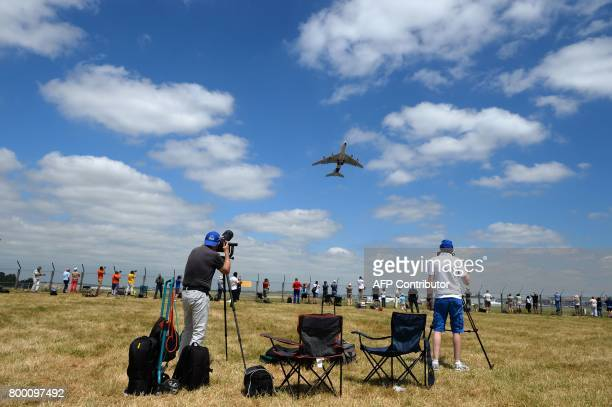 Plane spotters take pictures and videos of an Airbus A380 as it takes off during the International Paris Air Show in Le Bourget near Paris on June 23...