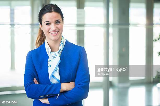 Plane stewardess looking at camera and smiling.